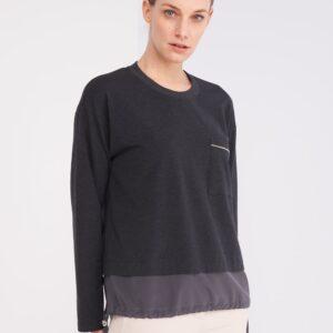 Anthrazitfarbenes Baumwoll Shirt. Leicht meliert und bekommt dadurch eine sportive Optik. Unterer Saum ist mit einem Seiden Teil verlängert, den man seitlich zusammenziehen kann. Am linken Brustteil befindet sich eine kleine aufgesetzte Tasche, welche mit einem Kettchen verziert ist.