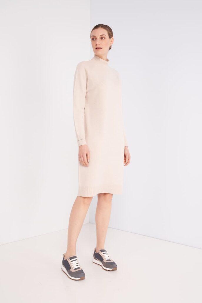 Beiges Strickkleid aus Kaschmir-Seide-Wolle Mix. Mit Stehkragen und Langarm. Am unteren Ende der Ärmeln mit einem typischen Peserrico Kettchen verziert. In Größe 36 (IT42) ist das Kleid hinten 105cm lang