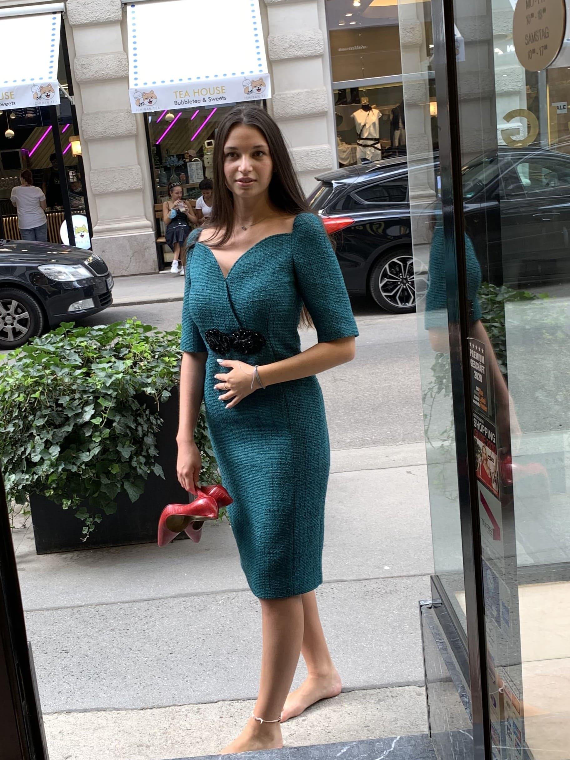 Dame trägt ein türkises Etuikleid von Boutique Moschino