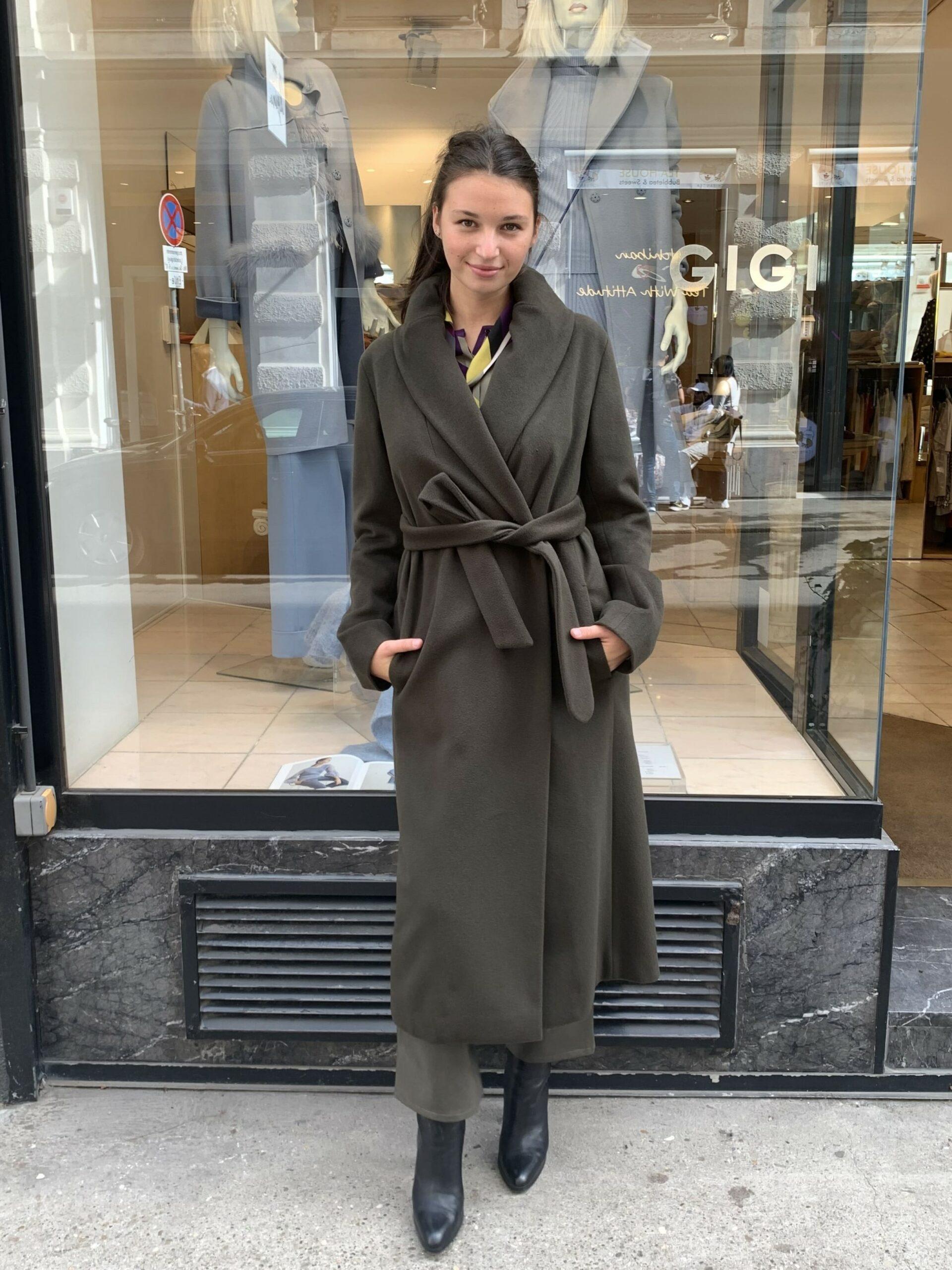 Eleganter dunkelgrüner Mantel aus Kaschmir-Wolle Mix mit einem drapierten Kragen und schmaler Silhouette. Die Taille wird mit einen Gürtel in gleichem Material und gleicher Farbe betont. Der Mantel wird mit einem sichtbaren und einem versteckten Knopf geschlossen.