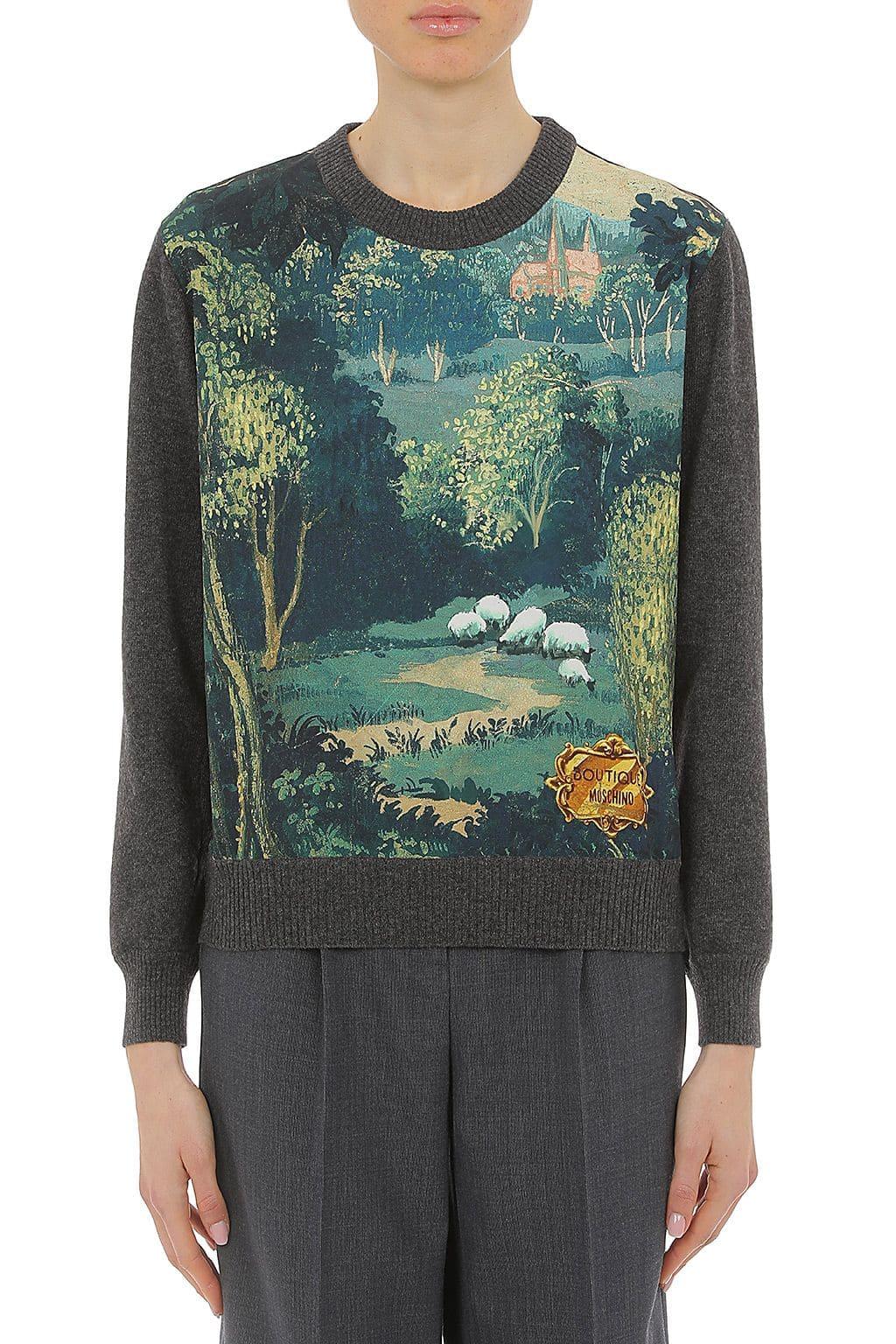 Dame trägt einen grau-grünen Pullover von Boutique Moschino