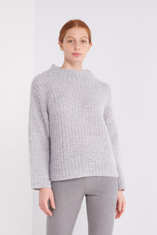 Hellgrauer Pullover mit stehenden Kragen in schöner Alpaka-Wolle Mix Qualität. Oversized. Mit etwas Glitzer innen. Der Pullover wirkt dick und grob gestrickt, fühlt sich aber ganz leicht an. Der Rückenteil hat in Größe 36 (42It) eine Länge von 62cm.