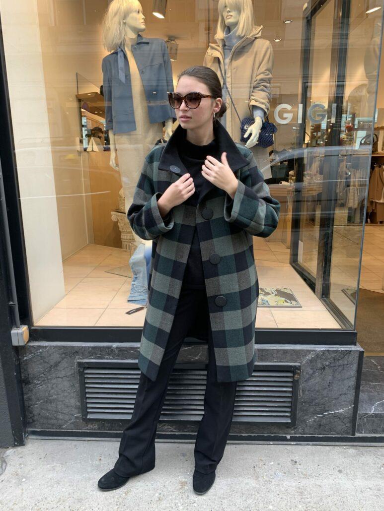 Dame trägt einen grün-schwarzen Mantel von Akris Punto