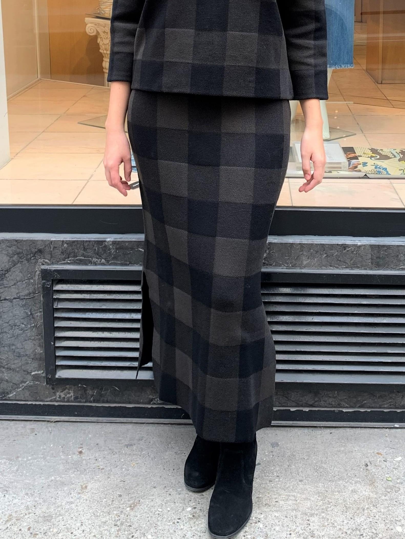 Dame trägt einen grün-schwarzen Bleistiftrock von Akris Punto