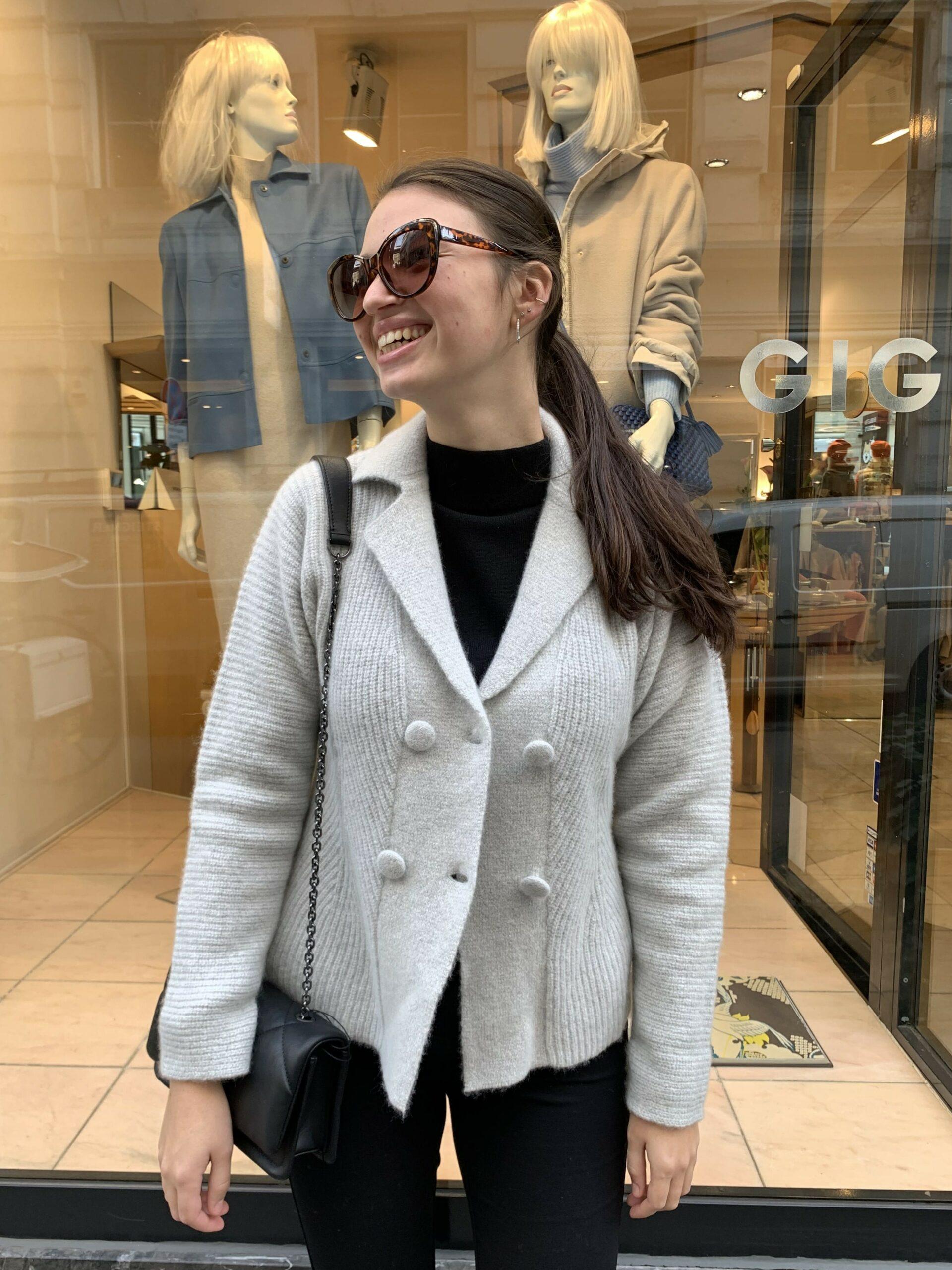 Dame trägt hellgraue Strickjacke von Emporio Armani