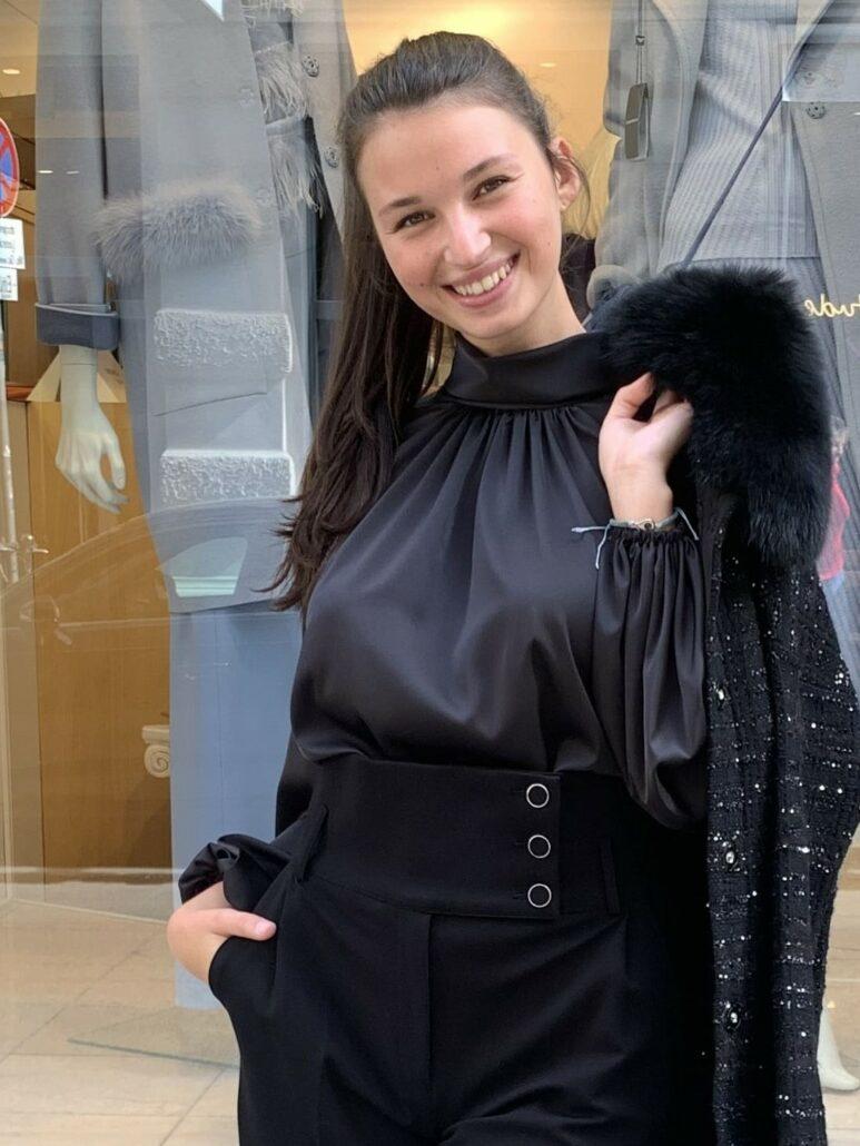 """Elegante schwarze schön fließende Bluse mit modischen breiten Ärmeln mit Gummisaum-Abschluß. Leicht drapiert im Kragen-Bereich und hinten mit zwei Knöpfen schließbar. Sehr raffiniert mit schwarzer """"Marlene"""" Hose und schwarzen Strickmantel von D.Exterior."""