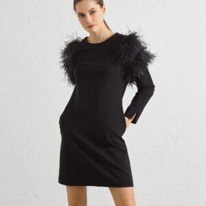 """Schickes schwarzes Kleid, welches die Figur umspielt und mit schönen Straußen-Feder Detail für etwas Überraschung sorgt. Die Federn sind ganz weich, leicht und passen perfekt unter einer Jacke oder einem Mantel. In Größe """"S"""" ist das Kleid 88cm lang und hat eine schicke 3/4 Armlänge. Das Kleid kann man elegant mit Pumps kombinieren oder mit derben schwarzen Boots ganz modisch anziehen."""