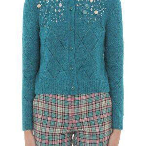Dame trägt eine kurze türkise Strickweste von Boutique Moschino